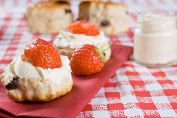 Scones, strawberries and clotted cream on a red napkin