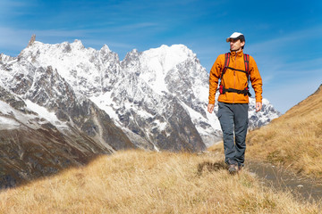 Male trekker walks along a mountain path, Mont Blanc Italy