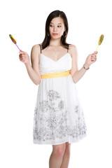 A beautiful asian woman choosing between two lollipops