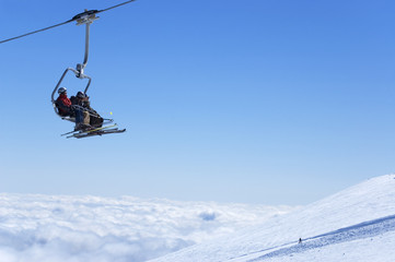 Chair lift with skiers at ski resort above the clouds