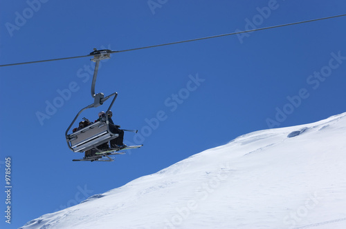 Chair lift with skiers at ski resort. Winter holidays