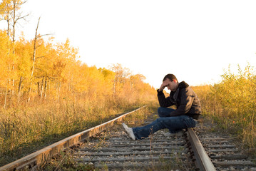 A man sitting on the railroad tracks, in a deep depression