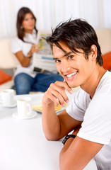 couple at home where he is smiling at the camera
