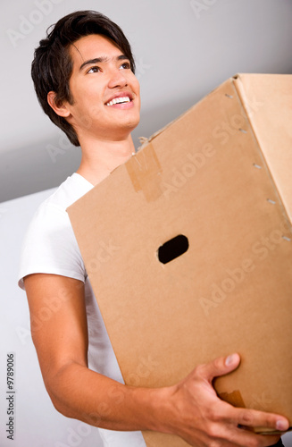 man moving homes smiling and carrying a carton box