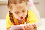 Cute little girl reading a book