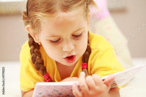 Cute little girl reading a book - 9791820