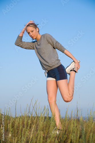 Athletics young woman stretching in a hilly meadow