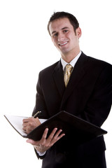 A young man in a business suit writing on a pad and smiling