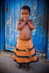 african girl in front of a blue door,