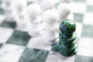 group of chess pawns, one ahead of the others