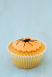 Halloween Cupcake with orange icing and spider crawling on top poster