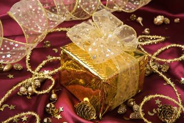 ein goldenes geschenk umgeben von deko auf satin