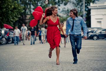 Runnng happy teenage couple in street