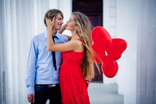 Teenage couple embracing holding bunch of baloons-hearts