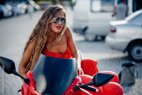 Beautiful woman in red posing on motorcycle