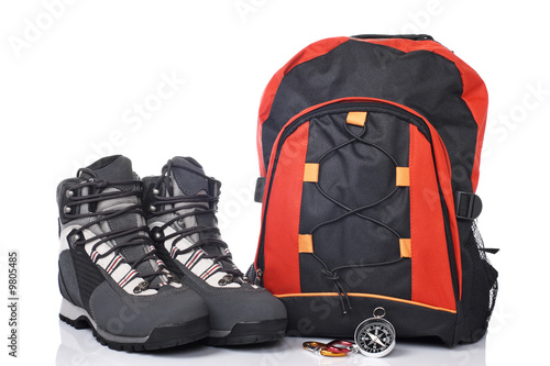 Hiking boots, compass, and backpack over a white background