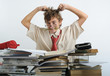 A teen behind of desk tearing his hair