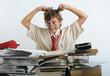 A teen behind of desk tearing his hair