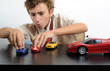 A teen playing with cars on a table