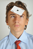 Young boy looking to an ace holded on his forehead poster