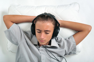 Young boy relaxing on pillow with headphones on ears