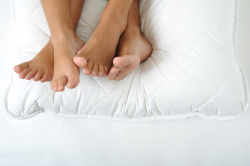 Foot resting on a white pillow, close up