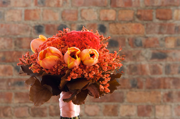 A colorful red and orange bridal bouquet of flowers
