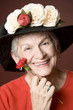 Senior woman in a red shirt and hat with flowers