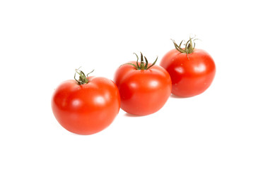 Three tomatos are isolated on a white background.