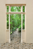 Doorway to a pathway through a lush green forest. poster