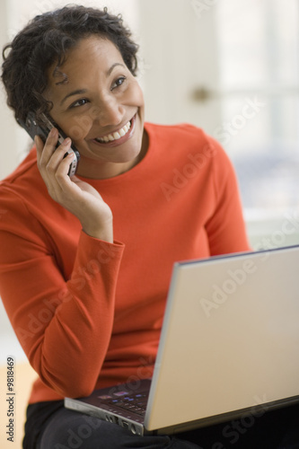 Beautiful young smiling  woman using cell phone and laptop