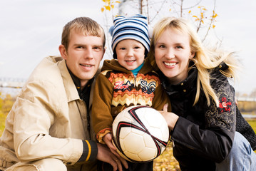 happy smiling family with a football ball outdoor