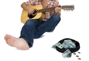 musician playing guitar with a hat full of money in front of him