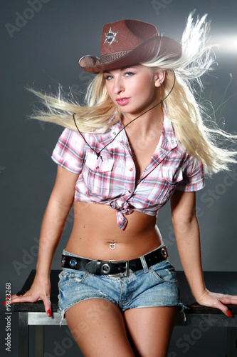 Sexy girl with cowboy hat on dark background