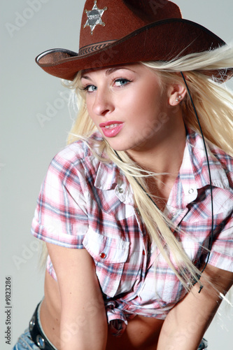 Sexy girl with cowboy hat on gray background