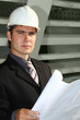 Business background: builder standing at building site.