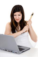 Junge Frau mit Hammer ist zornig wegen des Laptops