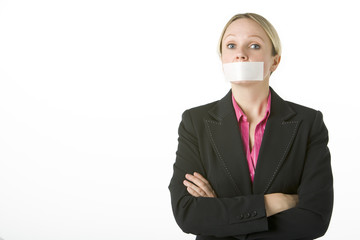 Businesswoman With Her Arms Folded And Mouth Taped Shut