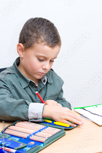 Portrait of a cute schoolboy drawing
