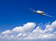 Civil aircraft travelling in deep blue skies with some cloud