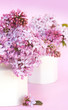 Gorgeous lilac blooms in small white vases.