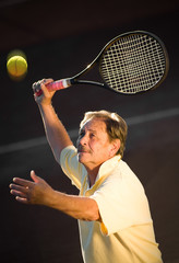 Active senior man in his 70s is playing tennis.