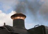 Smoke from the funnel of a restored steam locomotive poster