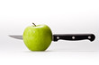 Green apple with a knife inside on white background