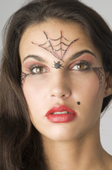 close up of young and nice brunette with spider web painted