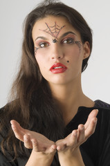 cute young woman with a spider web painted on face