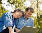 Affectionate mature couple at their laptop, outdoor setting poster