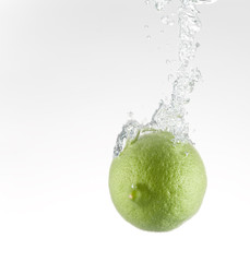 Single green lime pouring in water with  bubbles train