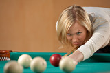 The beautiful blonde aims to a sphere in billiards poster