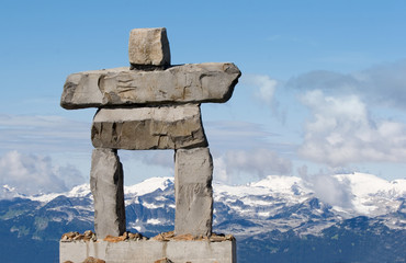rock inukshuk with mountains - inuit symbol - olympic symbol